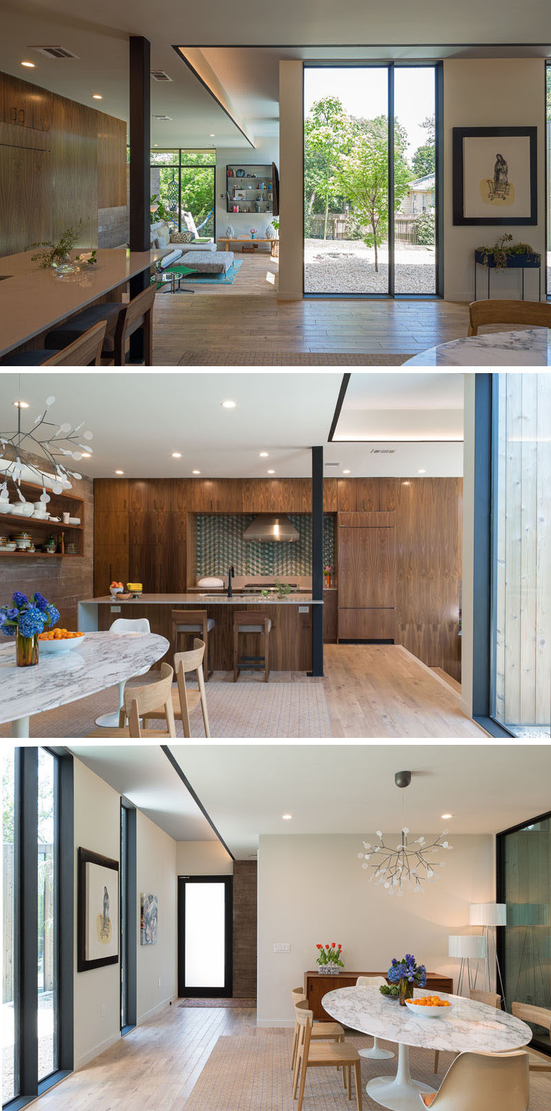 Stepped up from the living room in this house, is the kitchen and dining room. Wooden kitchen cabinets line the wall, with the island incorporating a column into its design. A sculptural chandelier helps to anchor the dining area in the space.