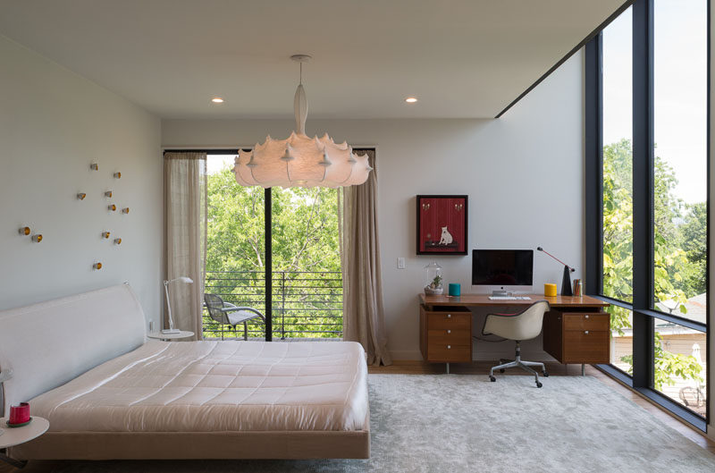 In this bedroom, large windows flood the room with light, and sliding glass doors provide access to the small balcony.