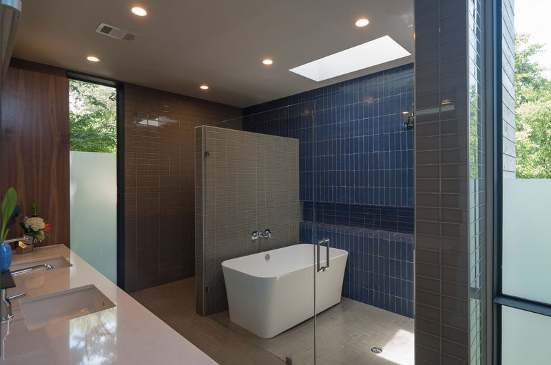 In this bathroom, the shower and bath are separated from the rest of the space with a glass wall/door, and the toilet is tucked behind the tiled wall.