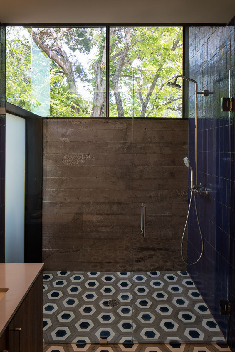 Poured-in-place concrete walls, geometric tiles and large windows make up the design of this bathroom.