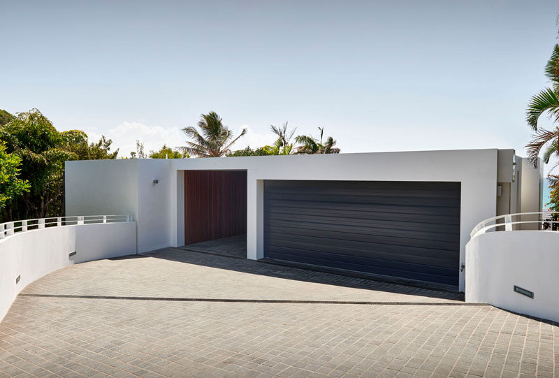 A dark garage door contrasts the white siding of this home.