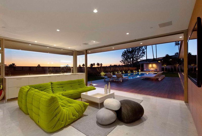 This comfortable living room has a splash of color with the lime green sofa, and it opens up for a view of the swimming pool.