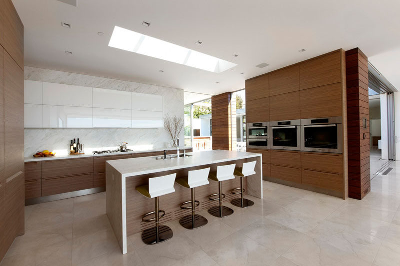 In the kitchen, the upper white cabinets match the island, with all of the other cabinets made from wood.