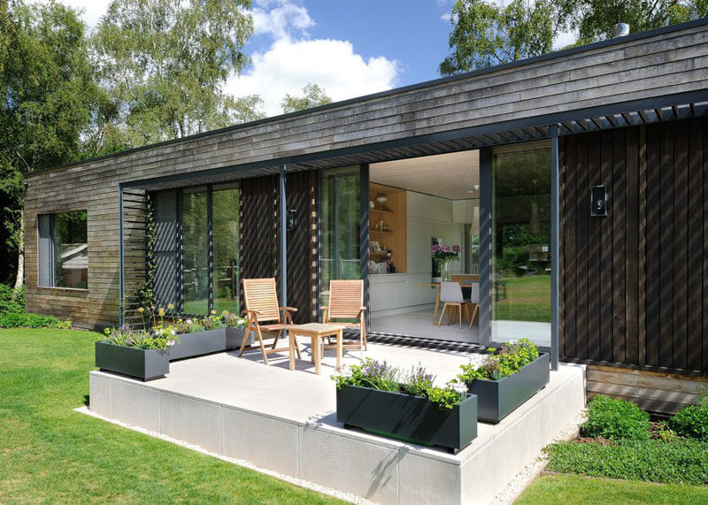 This contemporary mobile home has a small patio area with chairs and planters.