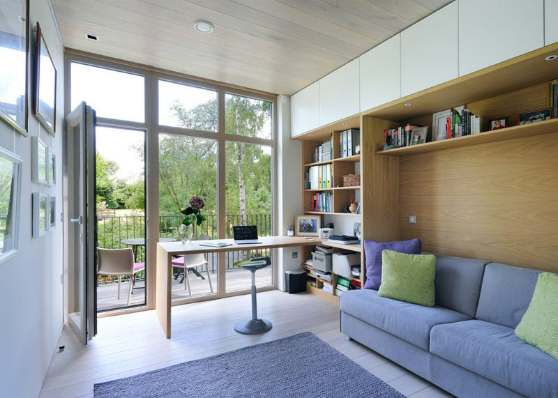This home office has built-in shelving and space for a sofa. It also opens out onto a little deck with enough room for a couple of chairs.