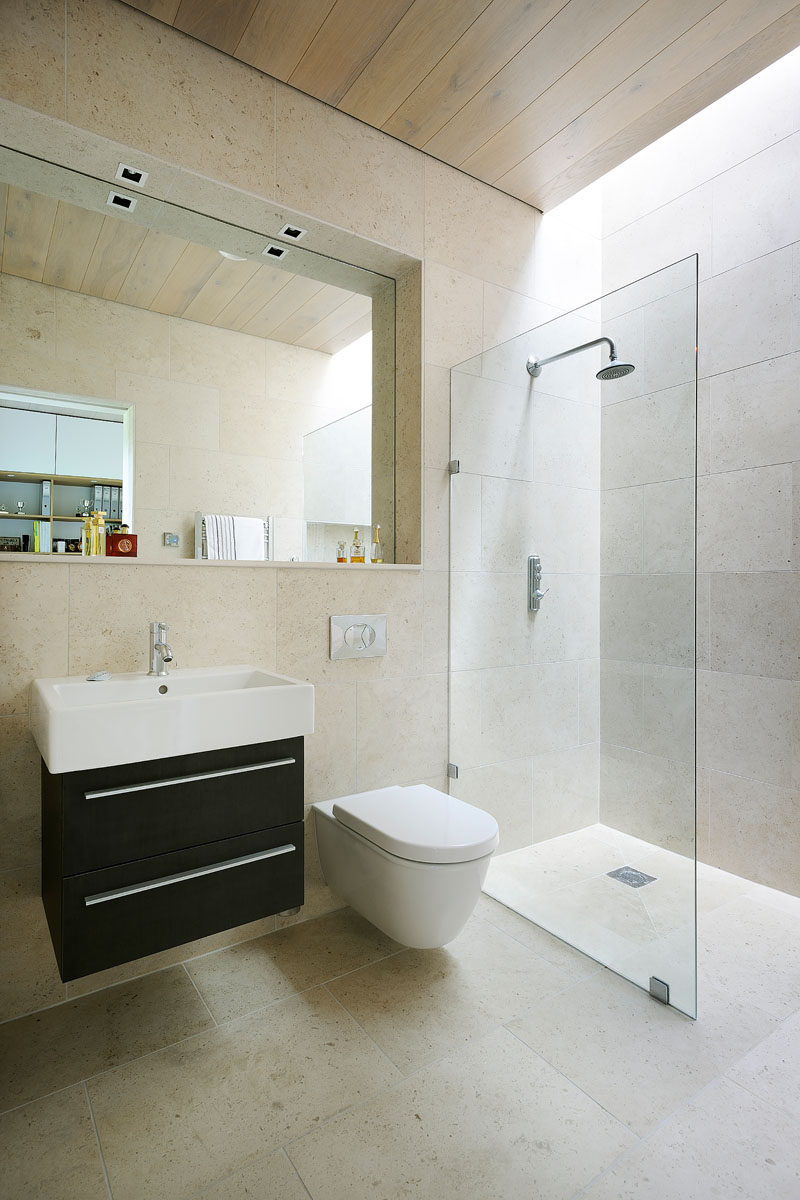In this bathroom, the mirror is set back, providing space for a ledge, perfect for displaying personal items. A skylight above the shower ensures that the space has as much light as possible.