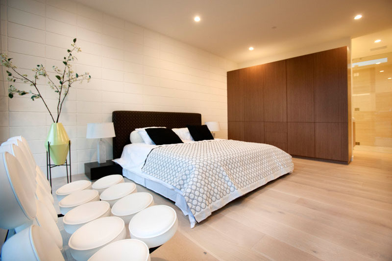 In this bedroom, the dark bed frame and wooden cabinetry contrasts with the white wall and light wood floor.