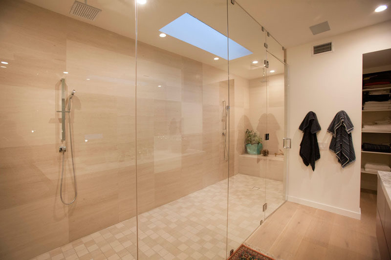 In this bathroom, a large glass enclosed shower stall is home to two separate showers.