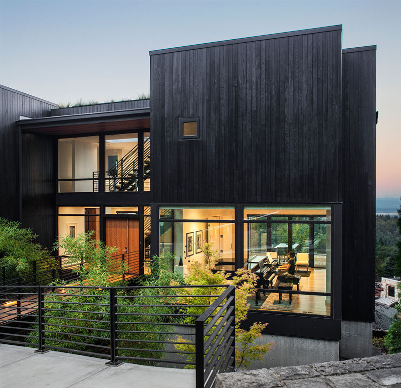 The exterior of the home is clad in black stained siding; reminiscent of Shou Sugi Ban or charred wood, which pays homage to the family's Japanese ancestry.