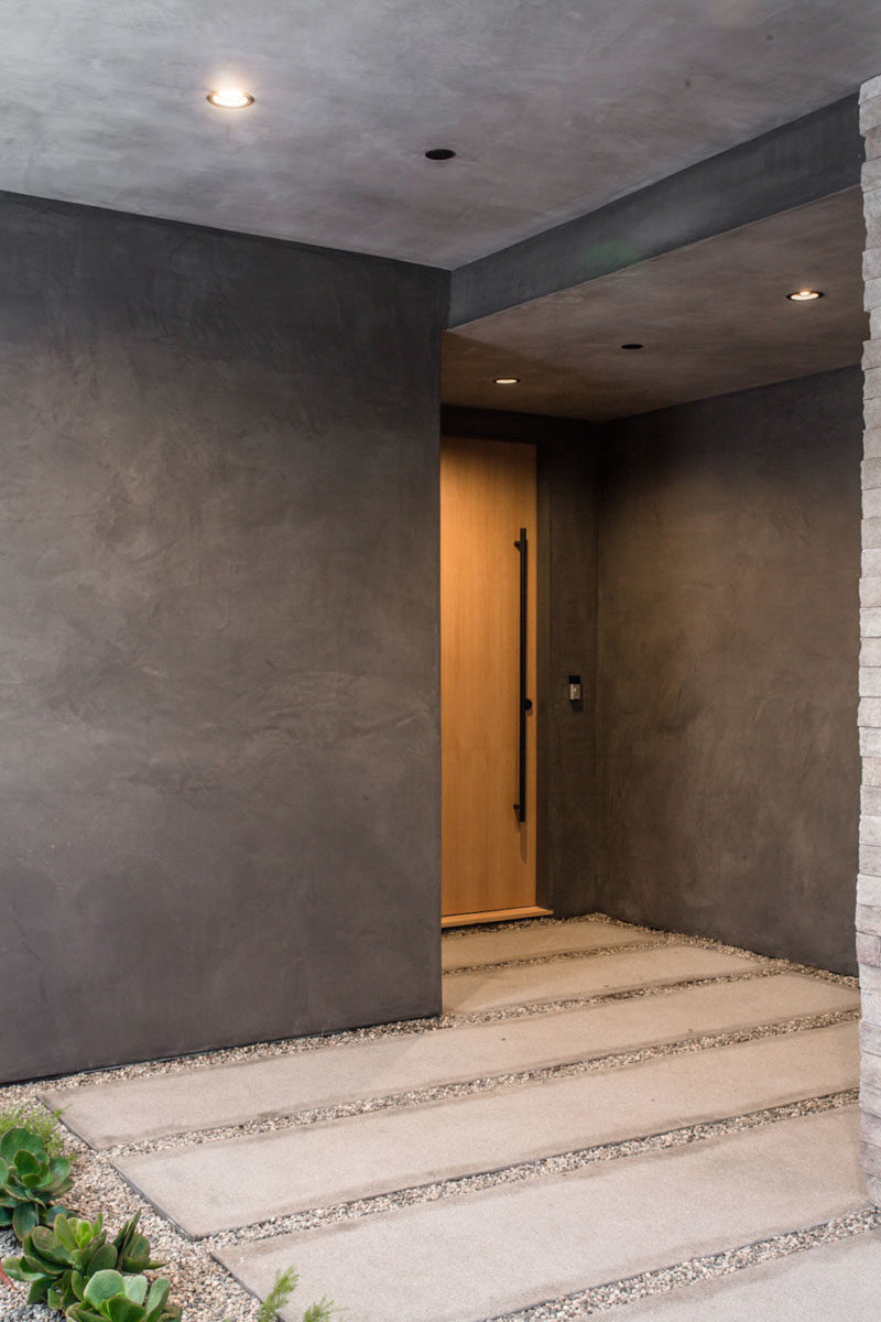 A landscaped concrete and stone path leadsyou to a large wooden door that stands out within its surroundings and welcomes you to the home.