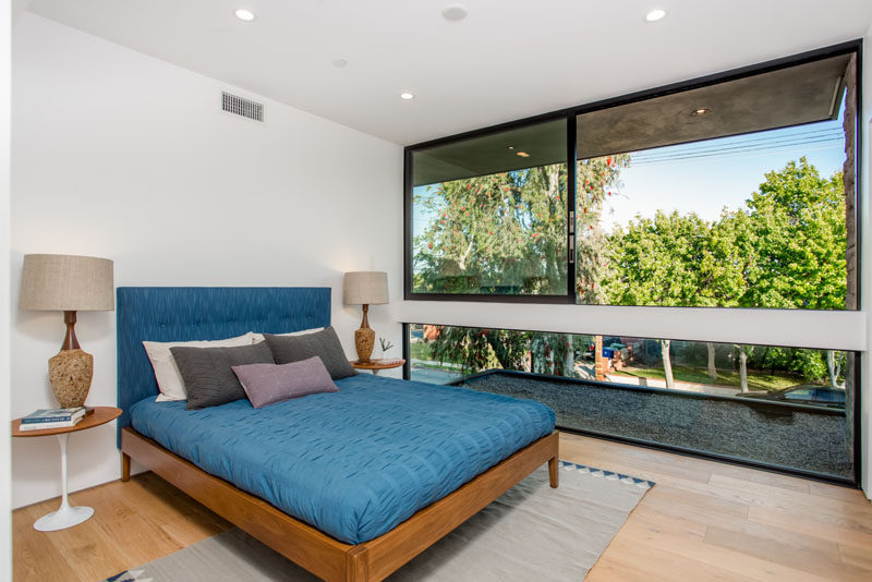 In this bedroom, large windows provide plenty of light and views of the trees and street.