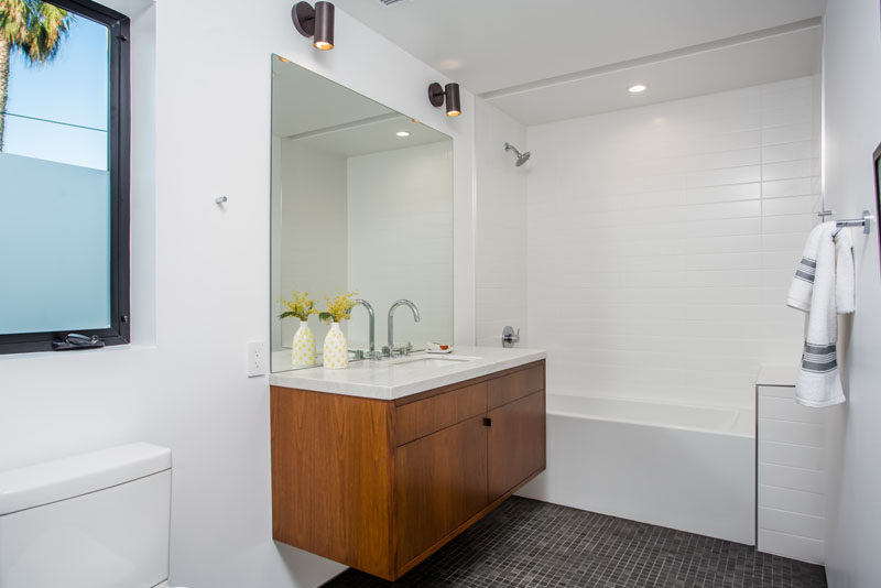 This bathroom features a partially frosted window for privacy, a shower/tub combo with, as well as a floating vanity.