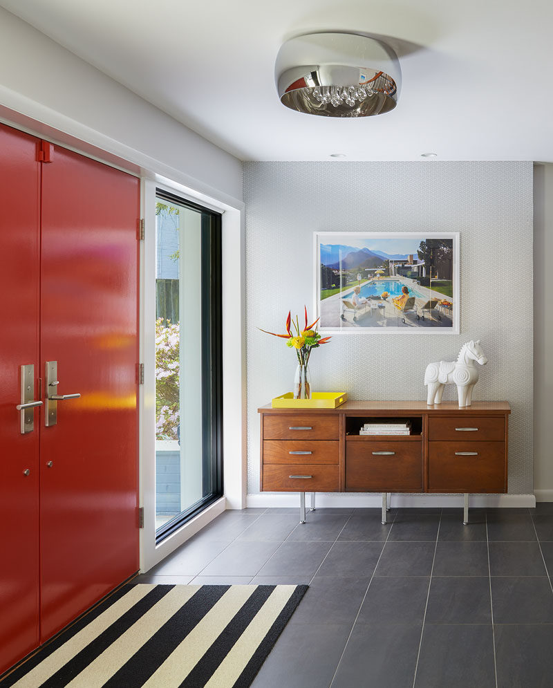 This home was renovated to include a bright red front door, with the foyer home to a mid-century modern style with a console table, a black and white striped rug and a framed retro photograph.