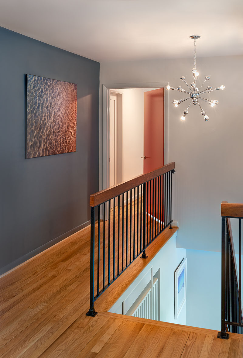 This hallway includes hardwood flooring, a dark gray accent wall and black metal railing topped with wood. A sputnik chandelier illuminates the space.