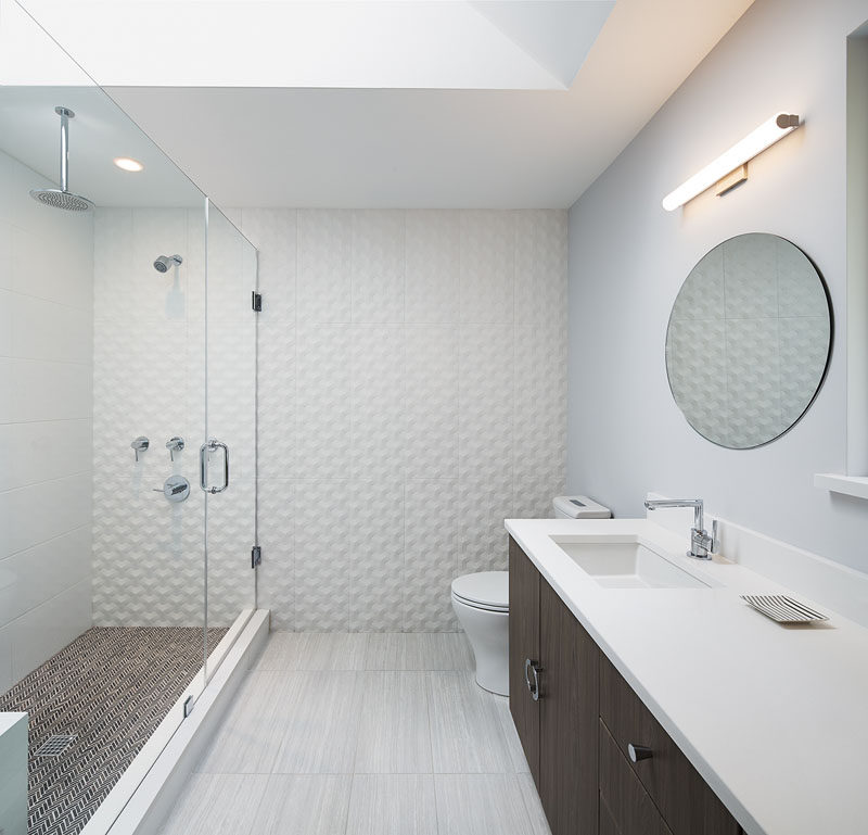 This bathroom design features a spacious walk-in shower with a rainfall shower-head, and a dark brown vanity adds contrast to the gray and white space.