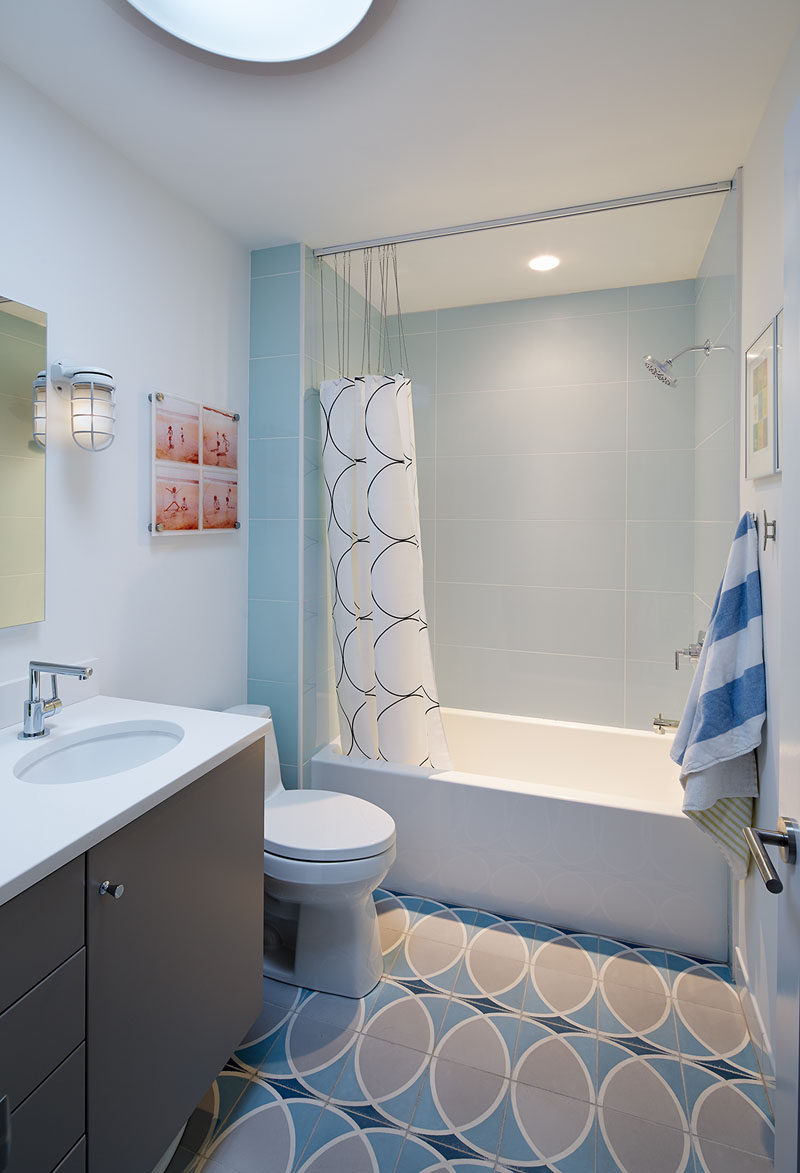 In this bathroom, light blue and gray create a serene look, with the circular pattern tile floor complementing the shower curtain and adds interest to the design.