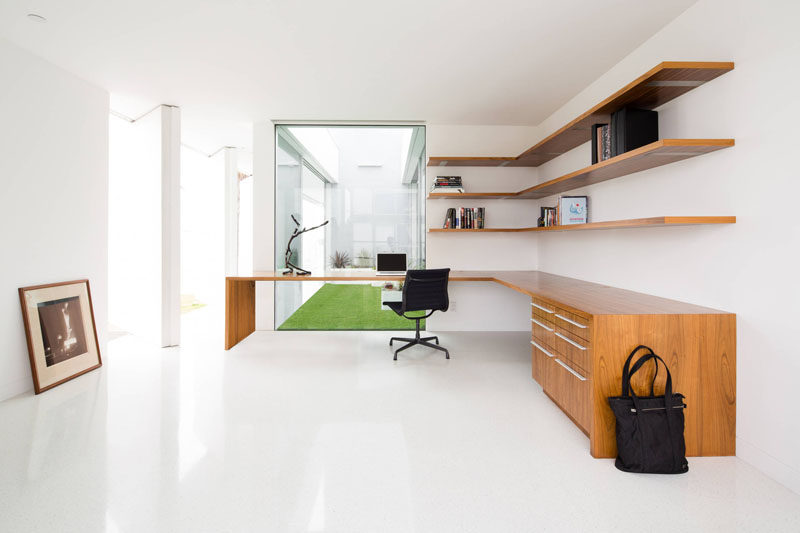 6 Design Ideas For Adding Corner Shelves To Your Home // Float Them --- Long, floating shelves running the length of this desk and tucked into the corner provide lots of extra storage in this home office.