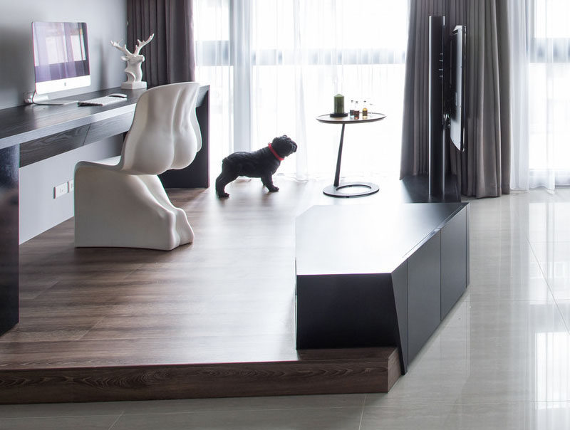 Apartment Design Idea - Divide Space By Slightly Elevating An Area. The designers of this apartment, split the living area by creating a platform, with a television and entertainment unit built-into it, acts as a further division by focusing attention on that spot rather than the work space behind it.