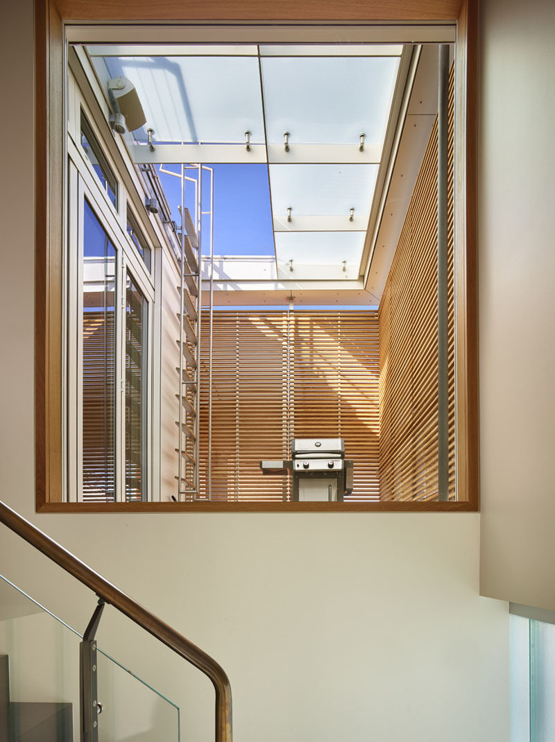 When walking up these stairs, a large window provides views of a small terrace with a barbeque (located off the kitchen), and a ladder that provides access to the roof deck.
