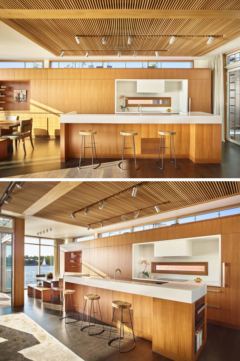 In this floating home, a wood slat ceiling feature anchors the living room and kitchen, and provides contrast to the surrounding white ceiling and walls. White touches has also been used in the kitchen, like on the island and cooktop area.
