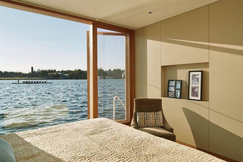 The bedroom in this floating home has a wall made of windows, allowing for picturesque views of the water.