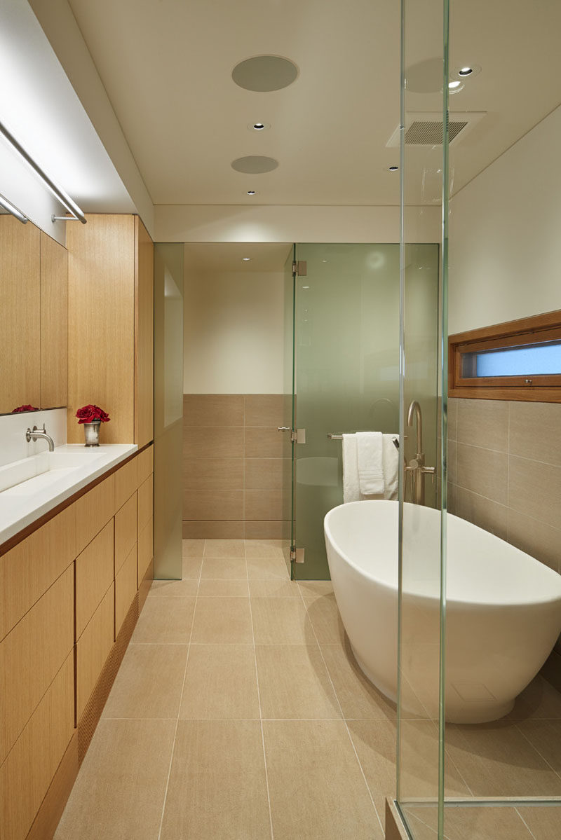 Frosted glass hides the toilet from the rest of this bathroom, and the flooring is made up of limestone tiles.