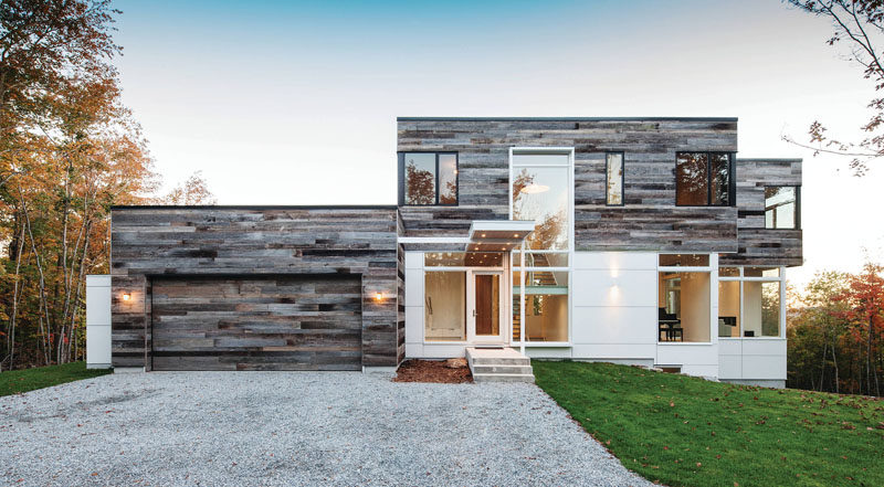 18 Inspirational Examples Of Modern Garage Doors // Covered in reclaimed wood panels, this garage door matches the exterior of the garage as well as the second level of the house.