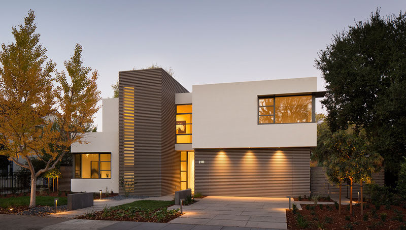 18 Inspirational Examples Of Modern Garage Doors // This garage door blends seamlessly right into the front of the house, with three lights highlighting the door at night.