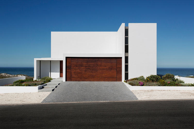 18 Inspirational Examples Of Modern Garage Doors // The dark wood paneled garage door is in stark contrast to the all white exterior and the light sand surrounding it.