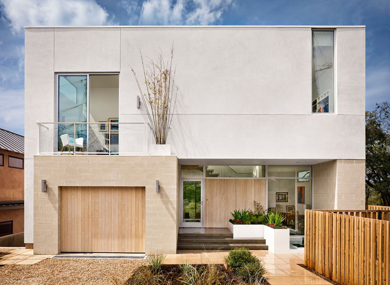 18 Inspirational Examples Of Modern Garage Doors // The light wood on this garage door matches the color of the bricks around it and the front door, creating a cohesive front exterior.