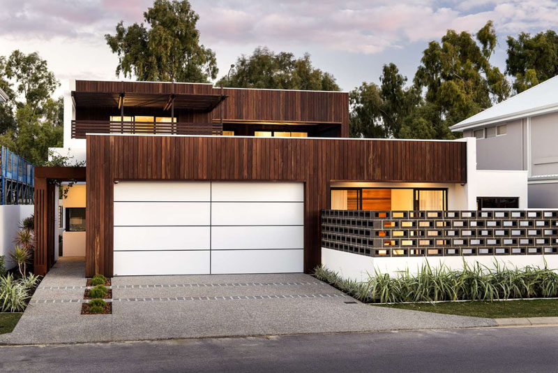 18 Inspirational Examples Of Modern Garage Doors // The bright white garage door with its dark lines, contrasts the wooden exterior in an unexpected and modern way.
