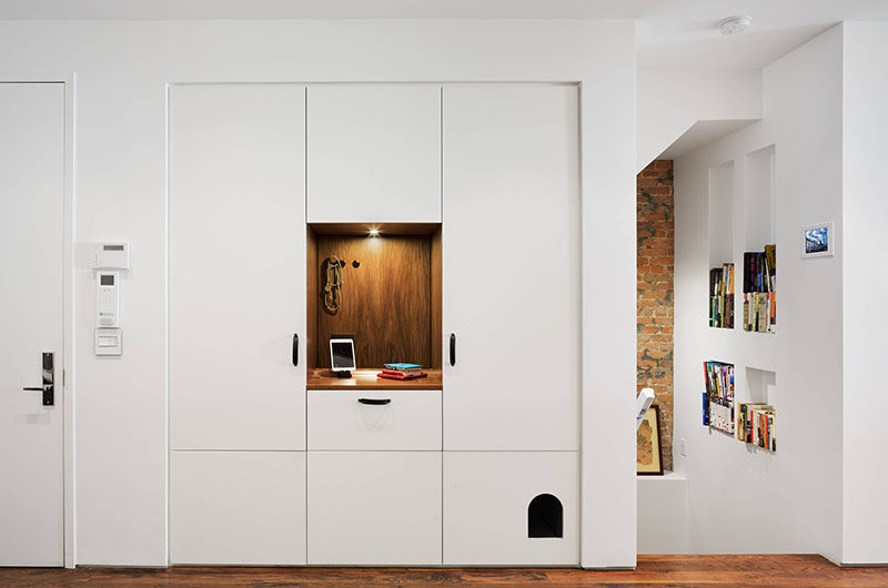 10 Ideas For Hiding Your Cats Litter Box // The litter box in this apartment is concealed within the entry way cabinet system.