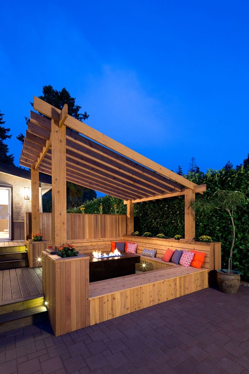 In the backyard of a renovated 1960s home in Vancouver, Canada, is this outdoor space that has built-in bench seating around an outdoor fire.