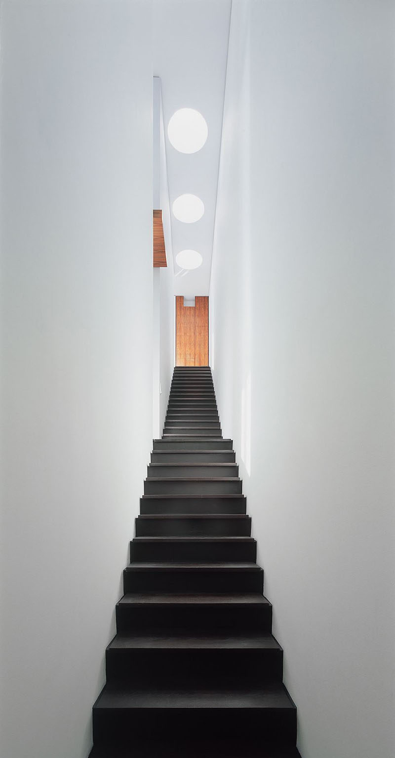 This single-flight stair way, which is lit from above, connects all three levels of this house.