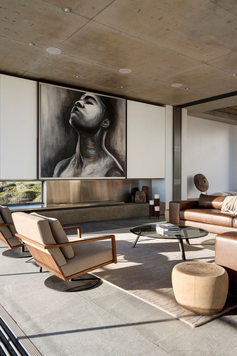 This living room is focused around a fireplace with a large piece of art hanging above it.