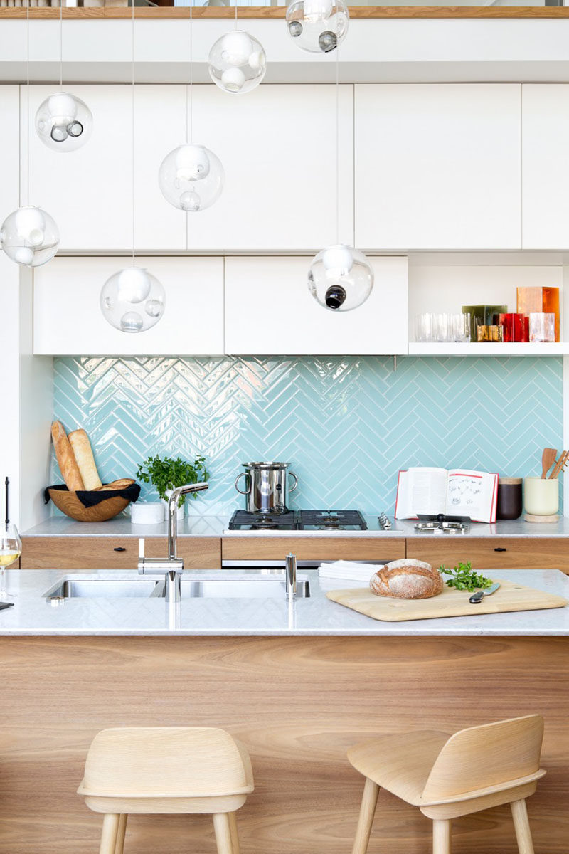 9 Inspirational Pictures Of Kitchens With Geometric Tiles // Shiny, light blue rectangular tiles laid out in a herringbone pattern create the backsplash of this Vancouver apartment.