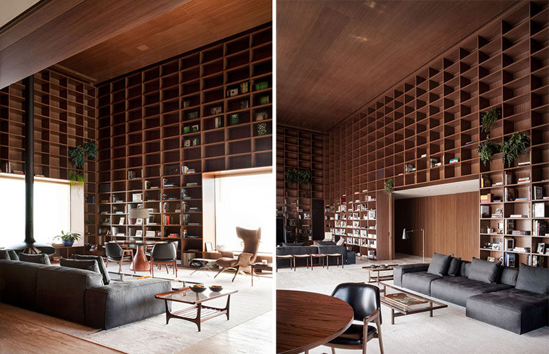 A double height room with floor-to-ceiling wooden shelves