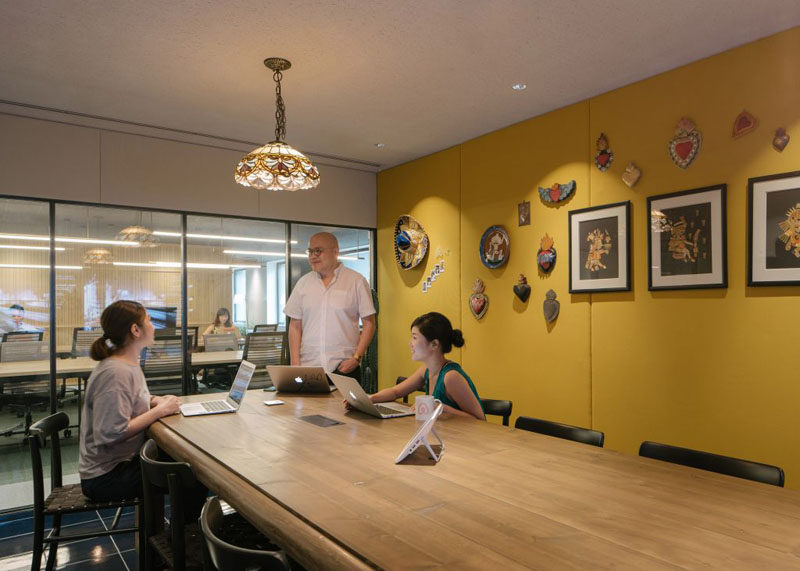 This boardroom has a bright yellow feature wall, large wooden table and a decorative pendant lamp.