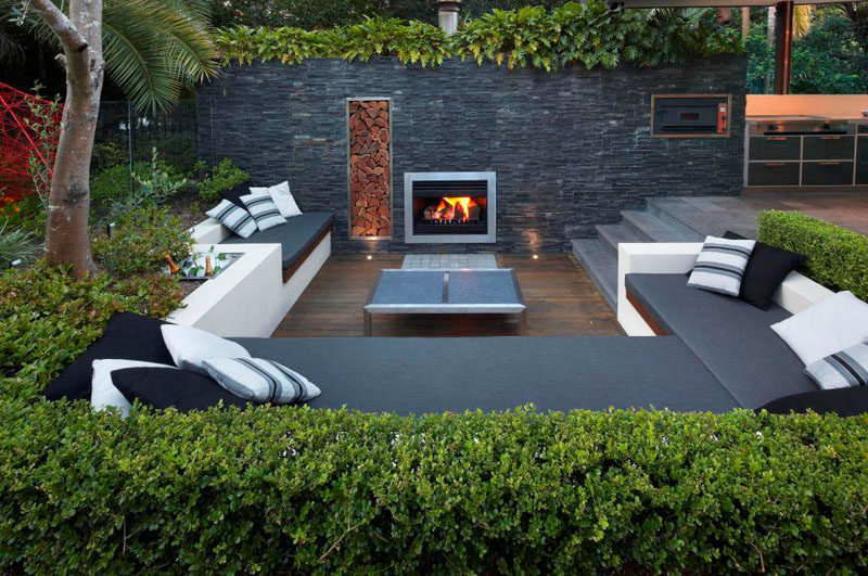 15 Outdoor Conversation Pits Built For Entertaining // Complete with a built in fireplace, wood storage, and a cooler, this sunken conversation pit would be great for both social gatherings and quite afternoons tucked up with books.
