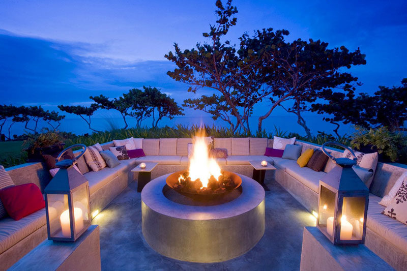 15 Outdoor Conversation Pits Built For Entertaining // Concrete benches covered in pillows surround a large fire pit that would throw off enough heat to let conversations flow late into the night.
