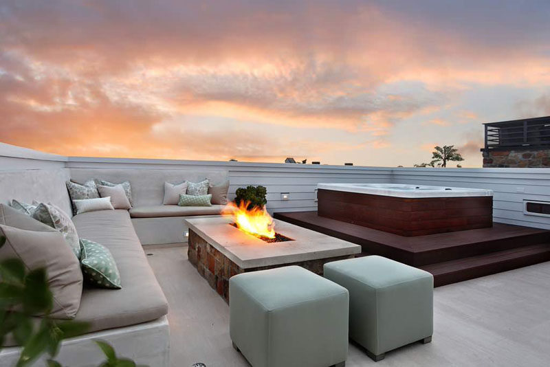 15 Outdoor Conversation Pits Built For Entertaining // This built-in rooftop conversation pit features a hot tub and fire, perfect for chilly nights. #ConversationPit #FirePit #YardIdeas