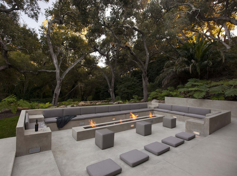 15 Outdoor Conversation Pits Built For Entertaining // This outdoor concrete living space contrasts the lush greenery surrounding it and makes it feel extra modern. #ConversationPit #FirePit #YardIdeas