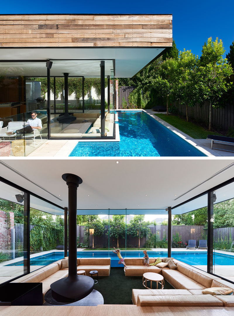 This Australian home features a small lap pool in the backyard and a sunken living room that sits at eye level with the pool.#SunkenLivingRoom #SwimmingPool #Fireplace #LivingRoom