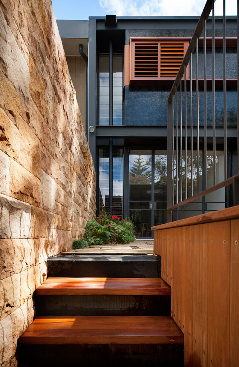 Sandstone walls have been paired with wood and black details to give this terrace home an updated look.