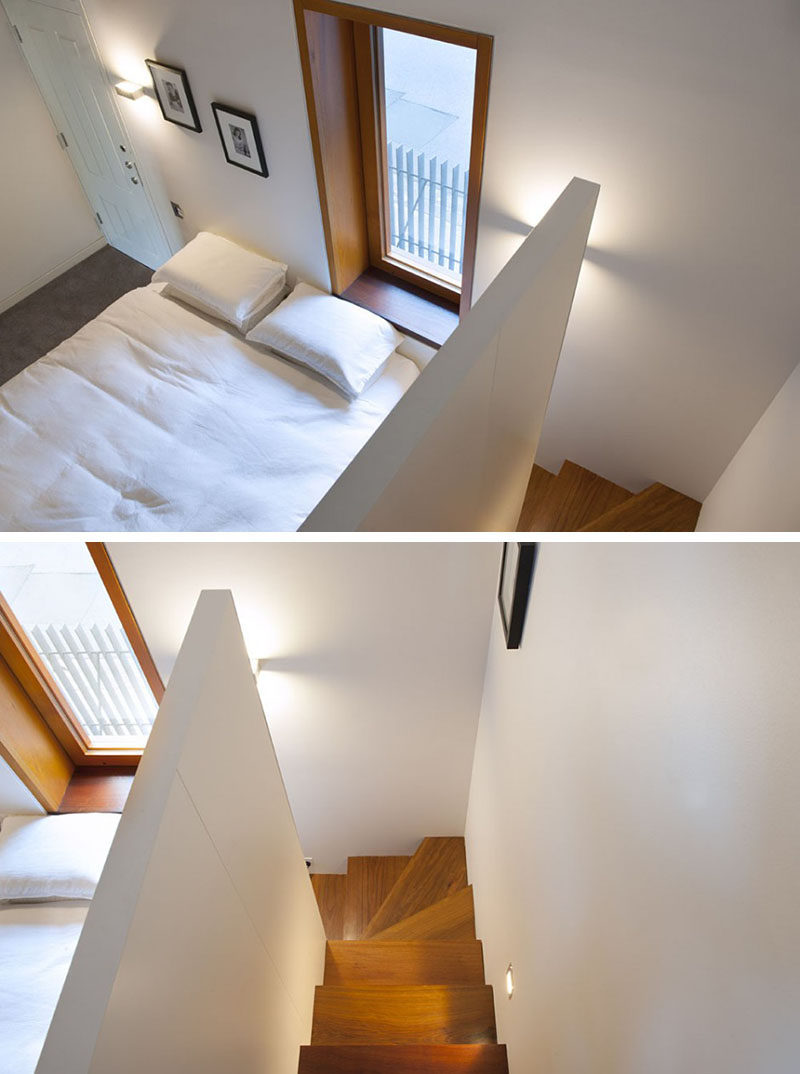 This bedroom has a wooden window frame and wooden stairs that contrast the white bedroom.
