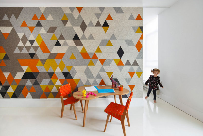 Multi-colored triangular pieces of felt add color to this accent wall that separate the child's bedroom from the rest of the home.
