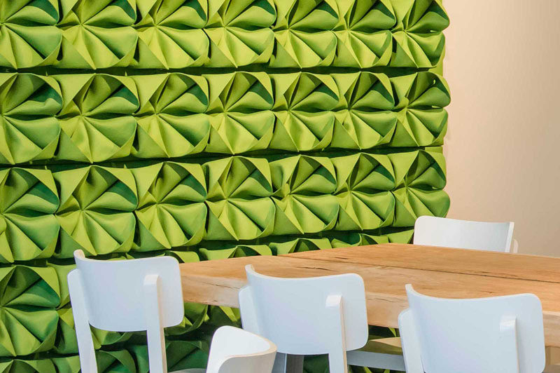 Intricately folded pieces of green felt attached to this accent wall give it dimension and texture, and brighten up the room.