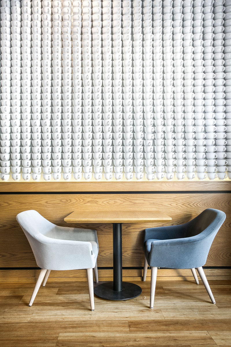 An accent wall in a coffee shop made from white teacups.