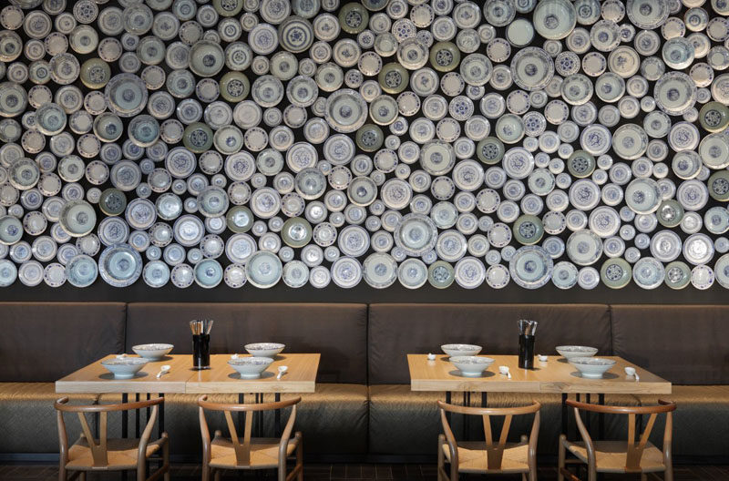An accent wall in a modern restaurant made from bowls and plates.