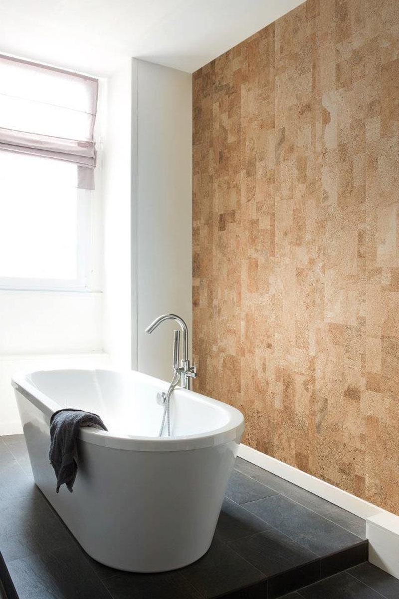 Cork panels have been used to create a natural accent wall in a bathroom.